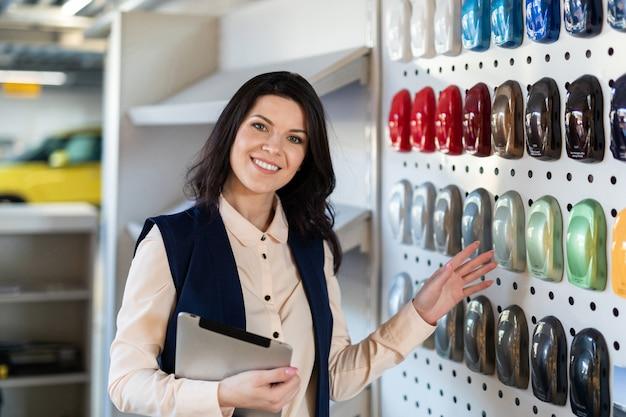 Vendedor profissional ajuda a escolher a cor de um carro no centro da concessionária