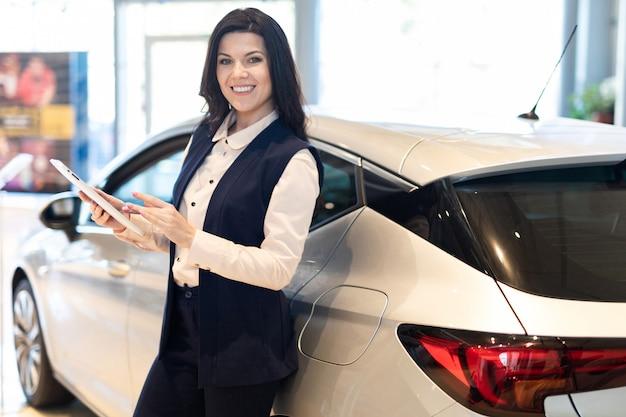 Vendedor profissional apresentar um carro novo no centro da concessionária