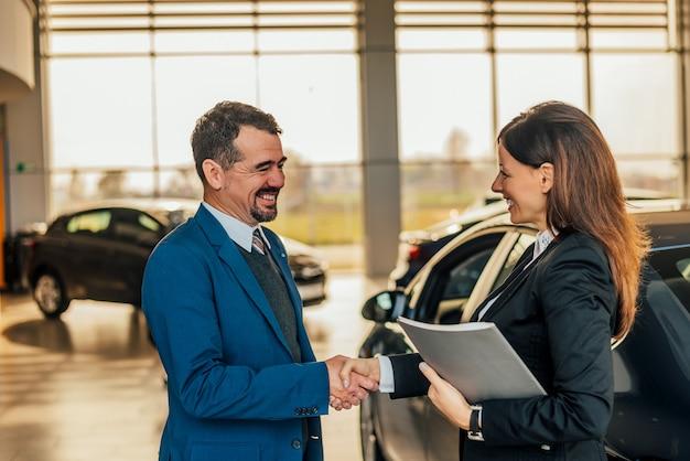 Vendedor que agita as mãos com o cliente na sala de exposições do carro.
