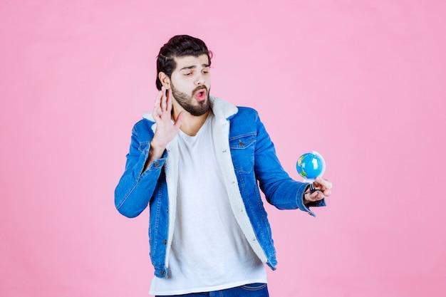 Vendedor segurando um mini globo e promovendo o produto