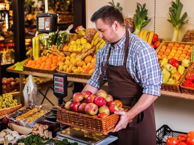 Vendedor segurando uma caixa com maçãs em pesos.