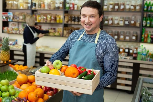 Vendedor sorridente segurando uma caixa de madeira com legumes e frutas na loja