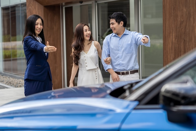 Vendedora asiática, dando as boas-vindas ao cliente do casal para verificar o carro na frente do showroom,