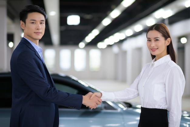 Vendedora asiática em negócios automotivos, aperto de mão com homem