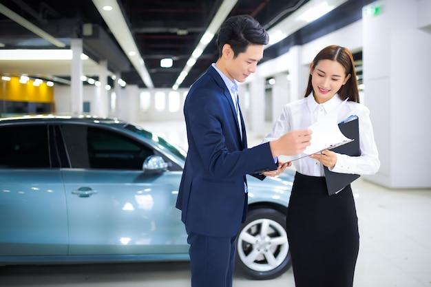 Vendedora asiática em negócios automotivos com cliente