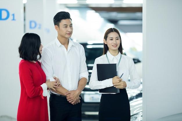 Vendedora asiática em negócios automotivos com clientes