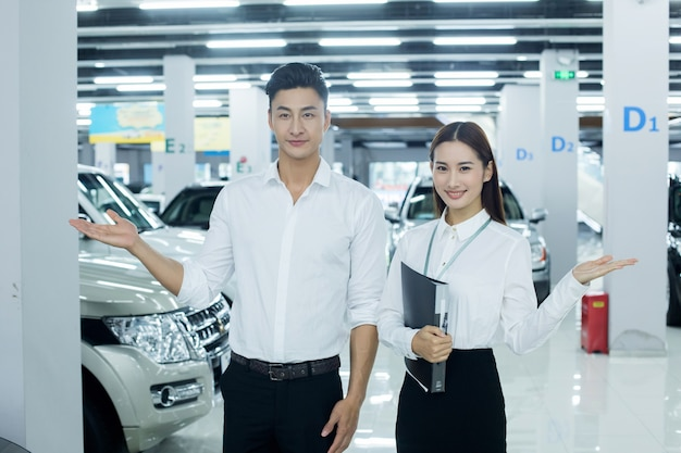 Vendedora asiática em negócios automotivos com homem