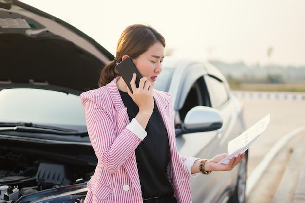 Vendedora asiática nova que escreve na prancheta com carro quebrado