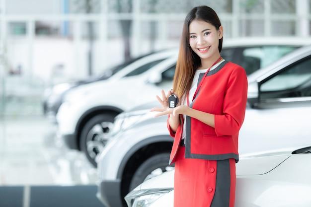 Vendedora asiática que dá a chave do carro sobre o fundo da feira automóvel, auto negócio, venda do carro.