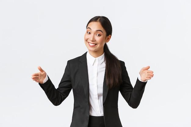 Vendedora asiática sorridente que vende produtos para o cliente, moldando um grande objeto e sorrindo amigável para a câmera. mulher de negócios apresenta seu projeto ao público, anuncia um apartamento grande, com fundo branco