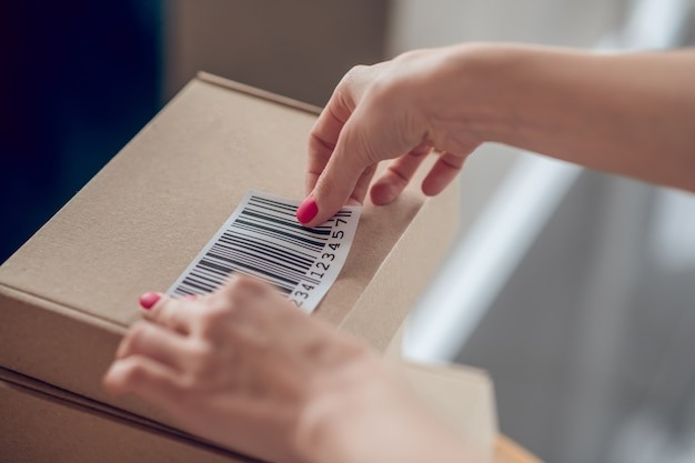 Vendedora caucasiana habilidosa preparando mercadorias para envio