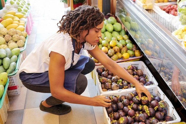 Vendedora, classificando as beringelas redondas