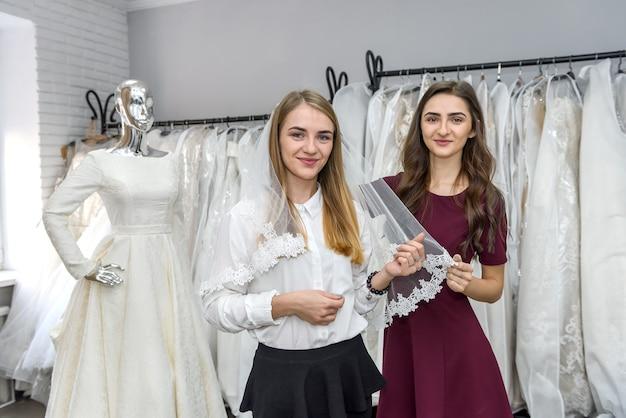 Vendedora colocando véu para jovem noiva na loja