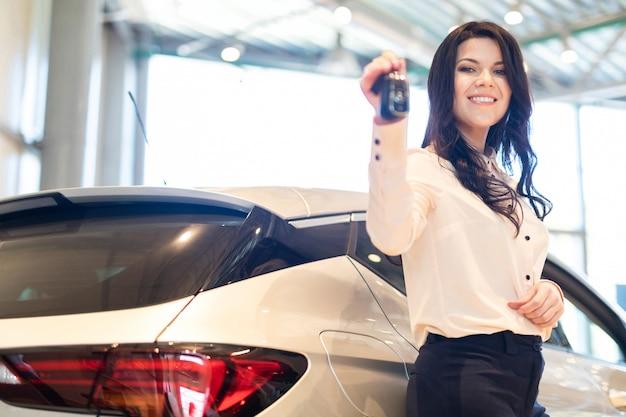 Vendedora com chave apresenta um carro novo no centro da concessionária
