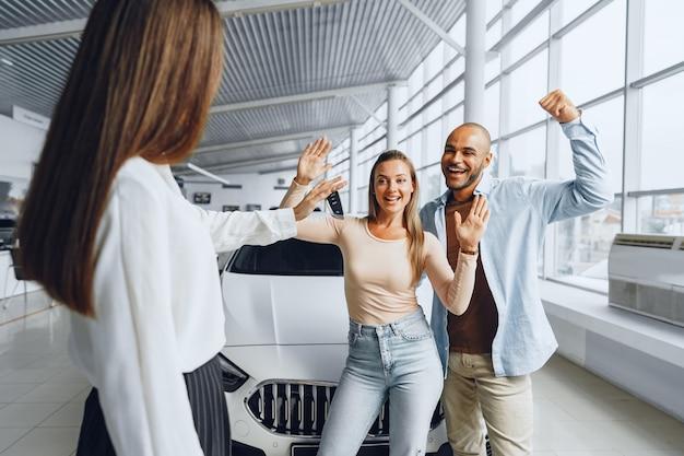 Vendedora de carros em uma concessionária conversando com compradores de clientes