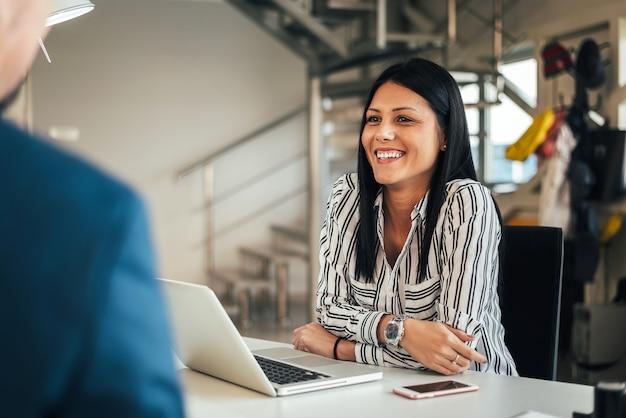 Vendedora de sorriso nova que fala com um cliente.