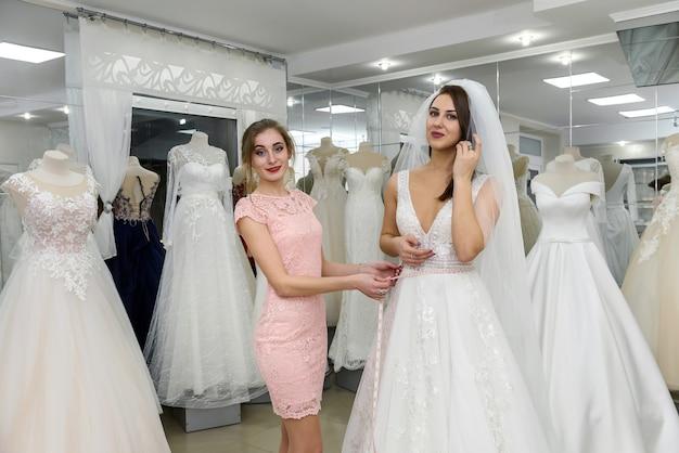 Vendedora em salão de casamento ajudando a jovem noiva