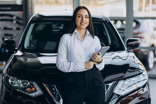 Vendedora em showroom de carros vendendo carros