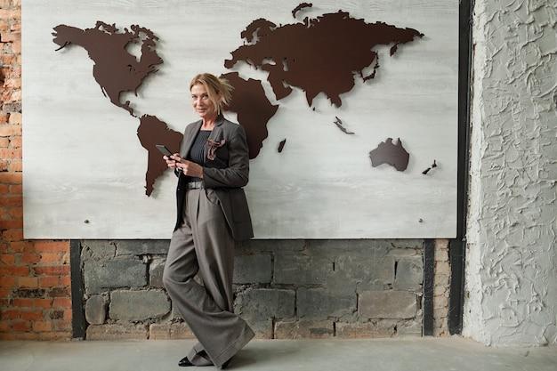 Vendedora madura de sucesso com calças largas em pé contra o banner do mapa-múndi no escritório e usando um gadget