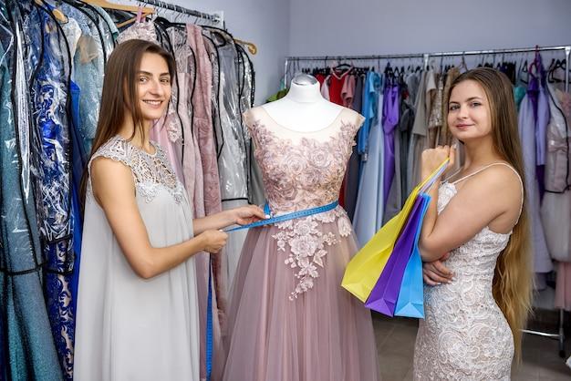 Vendedora mede vestido manequim com cliente na loja