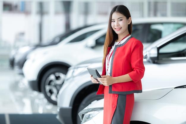 Vendedora nova asiática do carro que guarda a calculadora com uma exposição bem-vinda na sala de exposições.