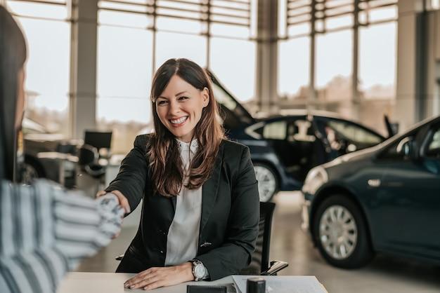 Vendedora que agita as mãos com o cliente no salão de beleza do carro.