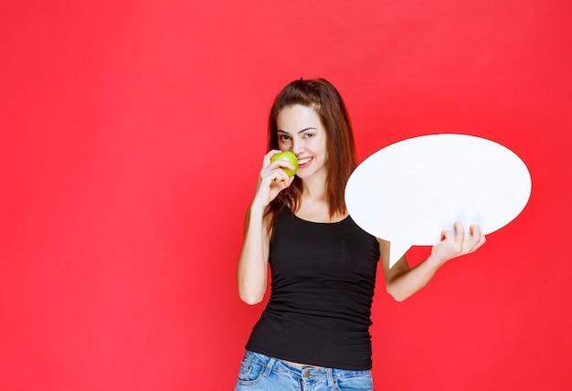Vendedora segurando uma maçã verde e um quadro oval de informações
