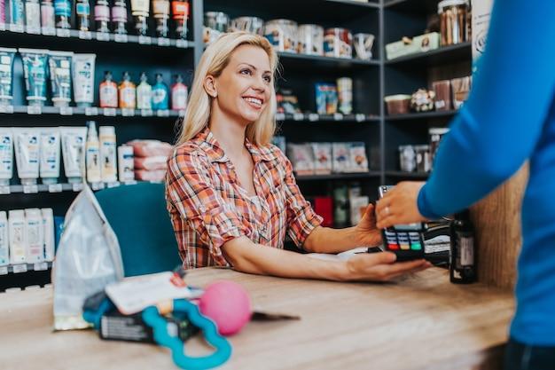 Vendedora sorridente, trabalhando no caixa da loja de animais de estimação. pagamento eletrônico com cartão.