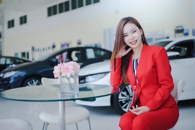 Vendedores de carros, mulheres bonitas, mulheres asiáticas que estão falando ao telefone com os clientes para vender carros novos em showrooms de carros