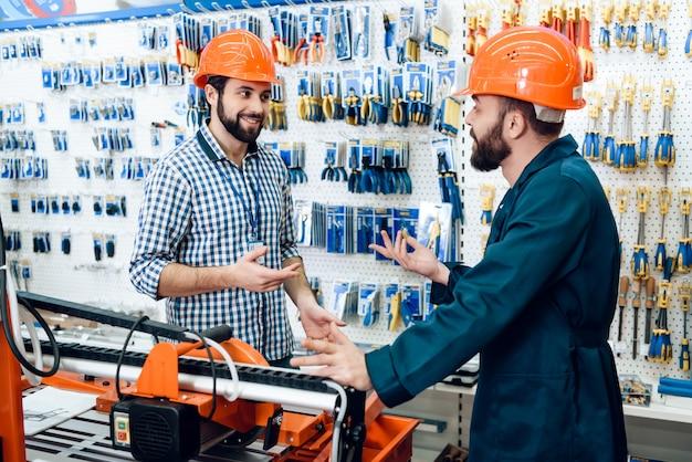 Vendedores em capacetes de construção estão discutindo equipamentos.