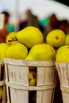 Vendendo peras em cestas no mercado do fazendeiro