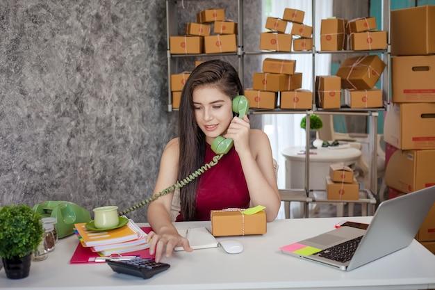 Vendendo produtos online. retrato de um telefone de mulher bonita falando com clientes para o transporte.
