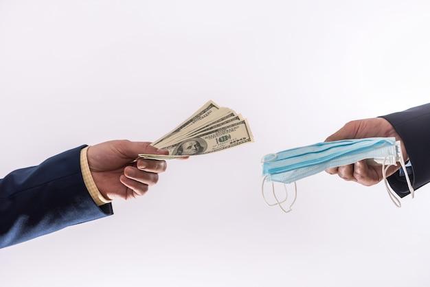 Vender coronavírus de quarentena de período de máscara facial médica caro e caro e dinheiro em notas de 100 dólares dos eua. tempo de covid 19