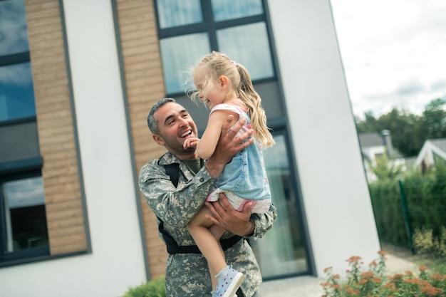 Vendo pai. menina fofa se sentindo incrível ao ver o pai retornando após o serviço militar
