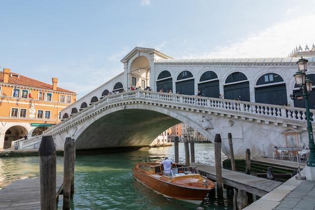 Veneza, itália - 1 de julho de 2018: vista panorâmica da ponte rialto (ponte di rialto) é a mais antiga das quatro pontes que medem o grande canal de veneza. paisagem de dia ensolarado de verão e céu azul
