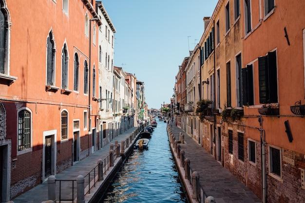Veneza, itália - 1 de julho de 2018: vista panorâmica do canal estreito de veneza com edifícios históricos e barcos da ponte. paisagem de dia ensolarado de verão