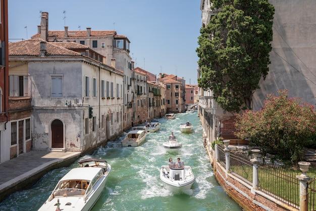 Veneza, itália - 1 de julho de 2018: vista panorâmica do canal estreito de veneza com tráfego de edifícios e barcos históricos da ponte foscari. paisagem de dia ensolarado de verão e céu azul