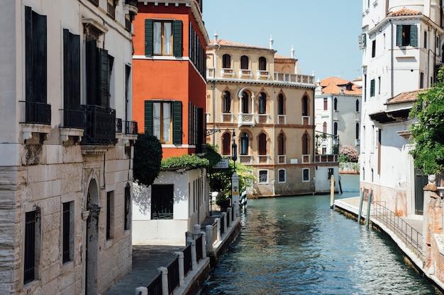 Veneza, itália - 1 de julho de 2018: vista panorâmica do estreito canal de veneza com edifícios históricos da ponte. paisagem de dia ensolarado de verão