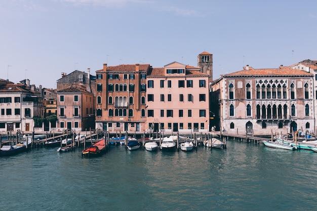 Veneza, itália - 1 de julho de 2018: vista panorâmica do estreito canal de veneza com edifícios históricos e barcos da ponte. paisagem de dia ensolarado de verão