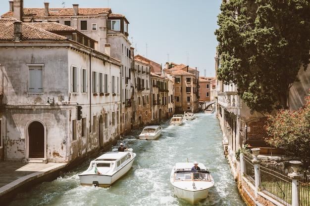 Veneza, itália - 1 de julho de 2018: vista panorâmica do estreito canal de veneza com tráfego de edifícios e barcos históricos da ponte foscari. paisagem de dia ensolarado de verão e céu azul