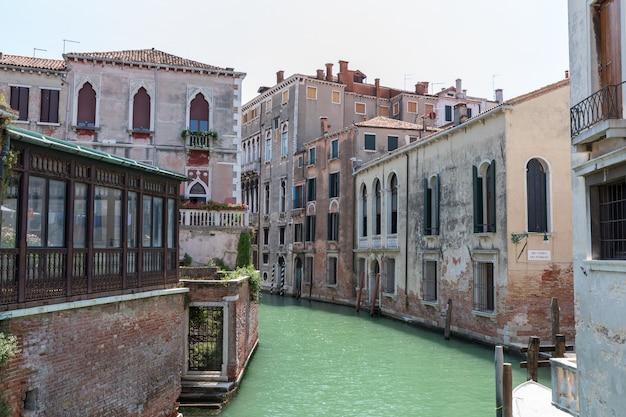 Veneza, itália - 1 de julho de 2018: vista panorâmica do estreito canal de veneza com tráfego de edifícios e barcos históricos da ponte. paisagem de dia ensolarado de verão