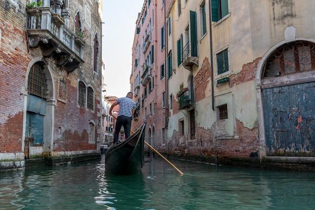 Veneza, itália - 2 de julho de 2018: vista panorâmica do estreito canal de veneza com edifícios históricos e gôndolas de outra gôndola. as pessoas relaxam na gôndola. dia ensolarado de verão e céu ao pôr do sol