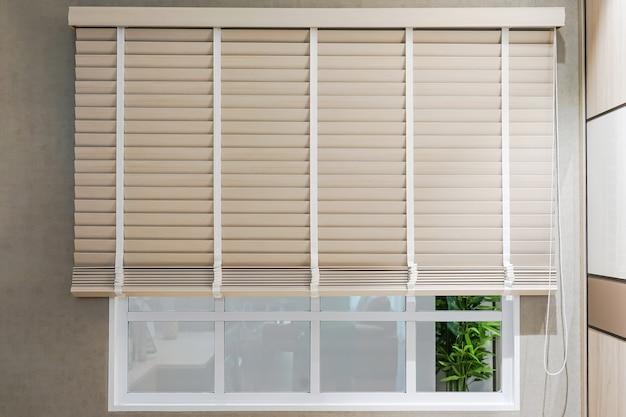 Venezianas de proteção solar de cor branca na janela em um dia ensolarado