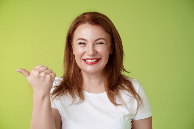 Venha visitar nossa loja alegre simpática simpática charmosa ruiva empresária de meia idade apontando polegar esquerdo suporte parede verde