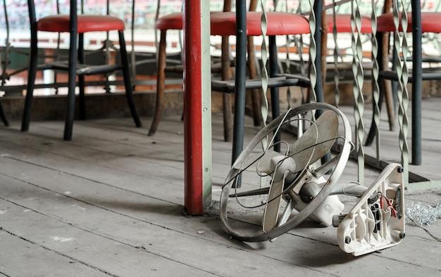 Ventilador antigo jogado no chão