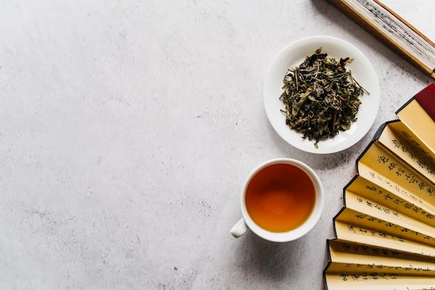Ventilador chinês com chá de ervas e folhas secas no fundo de concreto