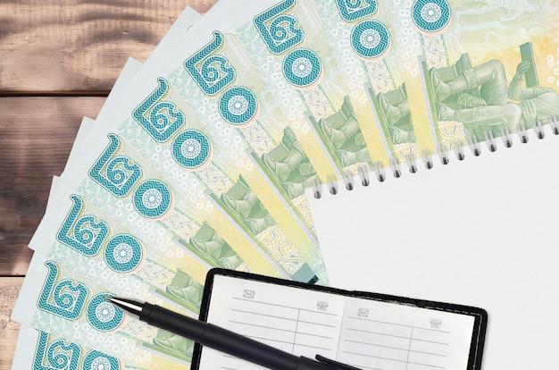 Ventilador de 20 contas de baht tailandês e bloco de notas com livro de contatos e caneta preta.