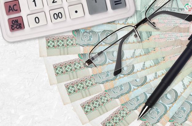 Ventilador de 20 notas de baht tailandês e calculadora com óculos e caneta