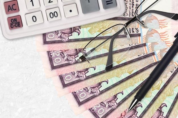 Ventilador de contas de rupias do sri lanka e calculadora com óculos e caneta.