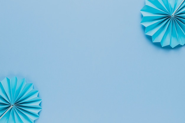 Ventilador de papel origami azul no canto do pano de fundo azul